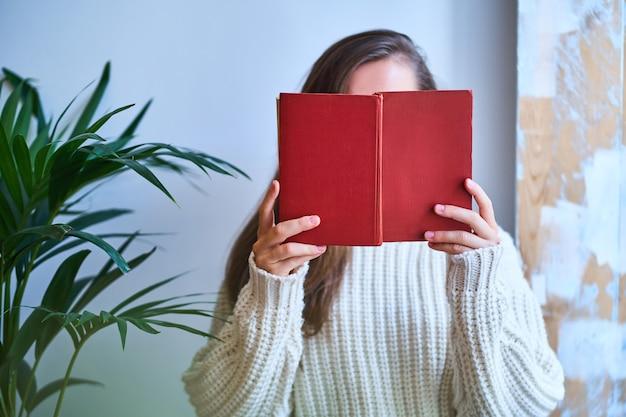 Femme confortable en pull chaud blanc tricoté en lisant un livre