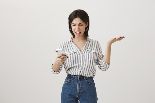 Femme confuse agacée regardant téléphone mobile et lever la main dans la consternation, se plaignant