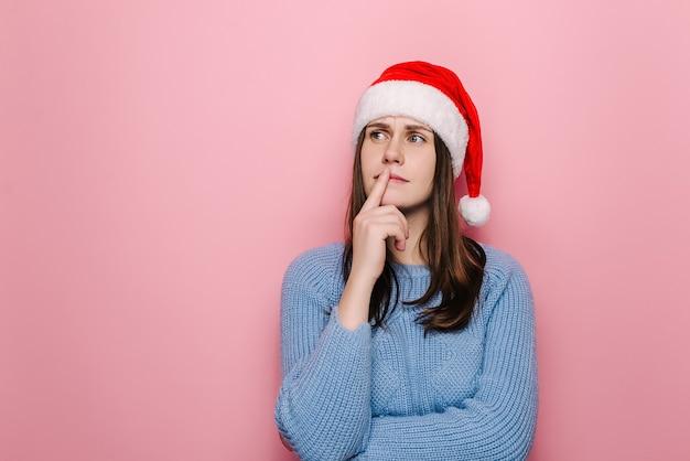 Femme confuse en chapeau de noël avec expression perplexe