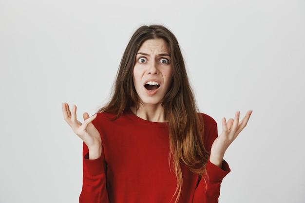 Une femme confuse et frustrée lève les mains avec consternation, laisse tomber la mâchoire en embuscade