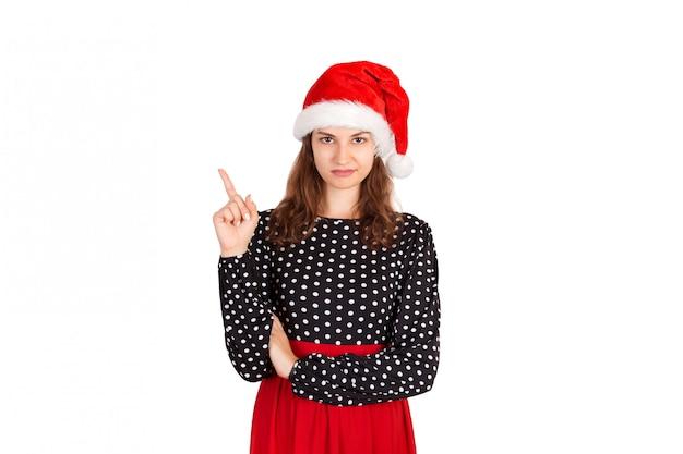 Femme confuse, pointant le doigt vers le haut. fille émotive au chapeau de noël père noël isolé