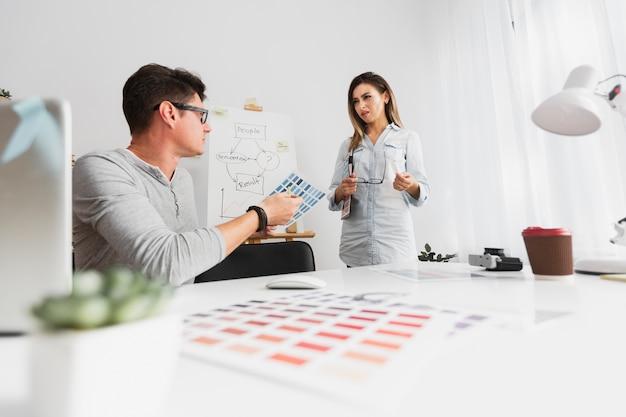 Femme confuse en regardant son collègue de l'entreprise