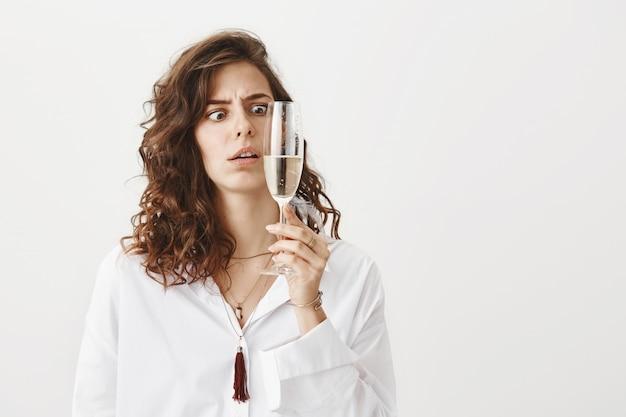 Femme confuse regardant verre champagne peu ivre