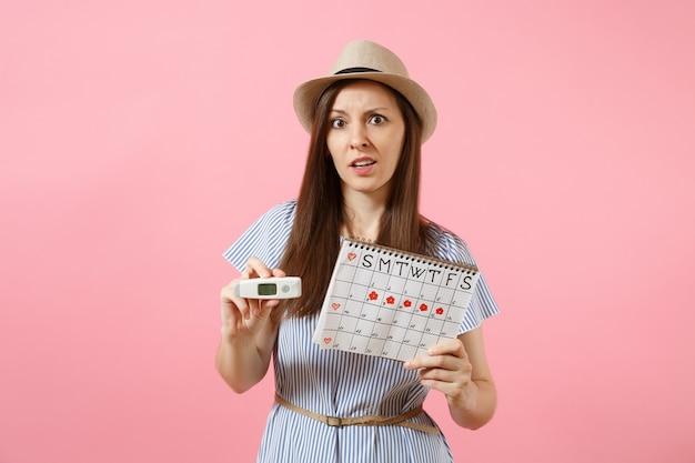 Une femme confuse en robe tient un thermomètre à la main, un calendrier des périodes féminines pour vérifier les jours de menstruation isolés sur fond rose. soins médicaux, concept gynécologique d'ovulation. espace de copie.