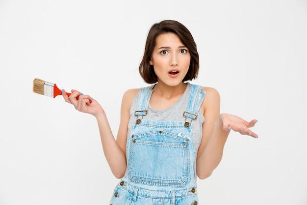 Femme confuse tenir pinceau et haussement d'épaules