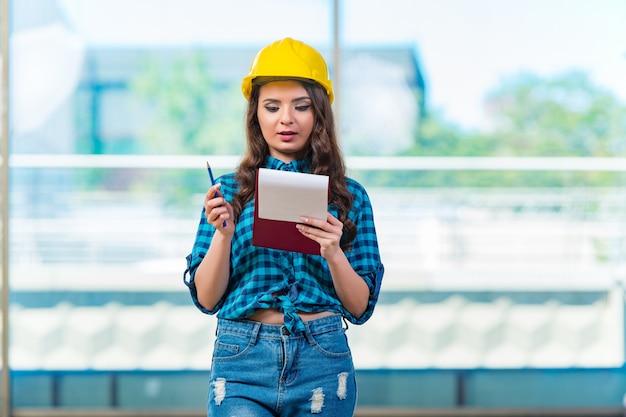 Femme constructeur prenant des notes sur un chantier de construction