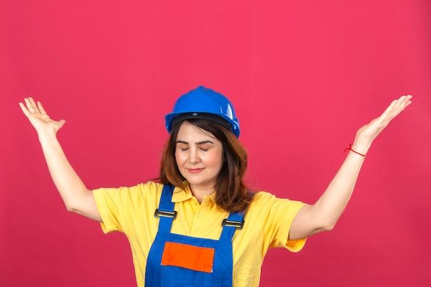Femme constructeur en uniforme de construction et casque de sécurité debout avec les yeux fermés, haussant les épaules, écartant les mains, ne comprenant pas ce qui s'est passé sans aucune idée et expression confuse sur isolé