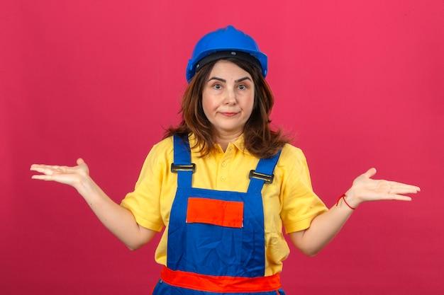 Femme constructeur en uniforme de construction et casque de sécurité en haussant les épaules, écartant les mains, ne comprenant pas ce qui s'est passé, expression désemparée et confuse sur mur rose isolé