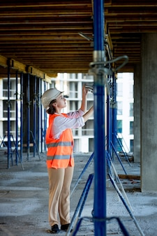 Une femme de construction confiante vérifie les fixations sur une structure monolithique. notion de construction.