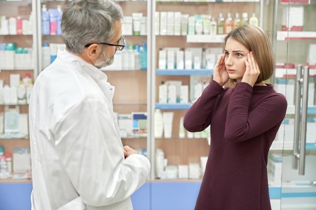 Femme consultant un pharmacien au sujet des maux de tête.