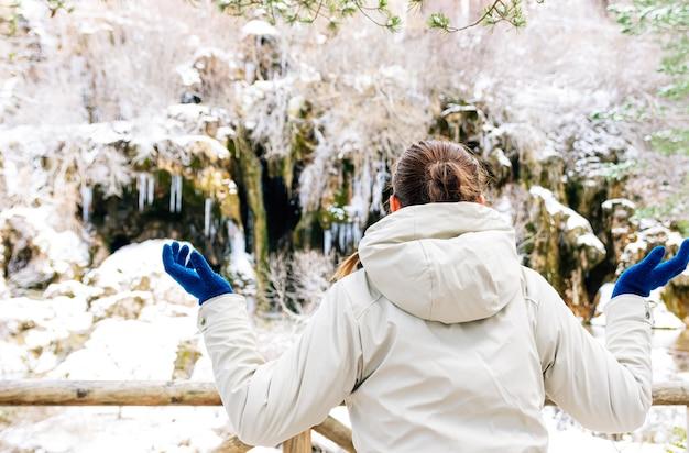 Femme contemplant la naissance de la rivière cuervo à cuenca, espagne. paysage enneigé en hiver.