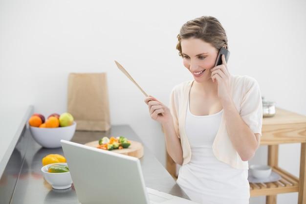 Femme de contenu téléphonant avec son smartphone dans la cuisine