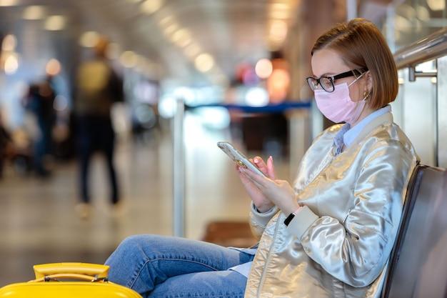 Une femme contrariée par l'annulation d'un vol, écrit un message à sa famille, assise dans un terminal d'aéroport presque vide en raison d'une pandémie de coronavirus