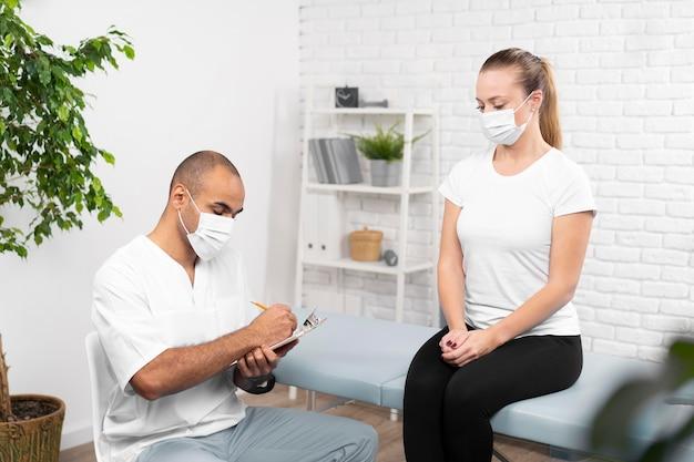 Femme de contrôle de physiothérapeute masculin