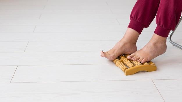 Femme en convalescence après un coronavirus avec appareil de massage des pieds