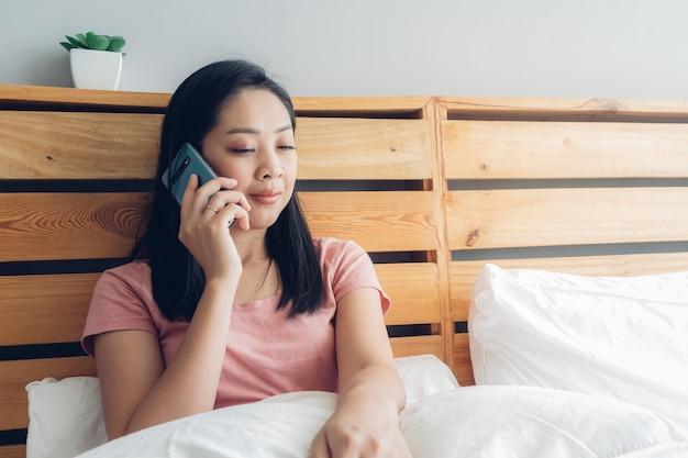 La femme a une conversation téléphonique sur son lit le matin.