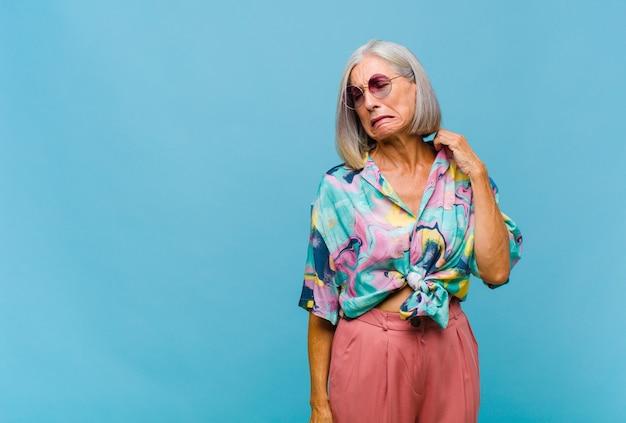 Femme cool d'âge moyen se sentant stressée, anxieuse, fatiguée et frustrée, tirant le cou de chemise, à la frustration de problème