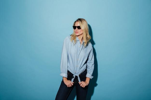 Femme cool en chemise et lunettes de soleil posant tout en regardant ailleurs