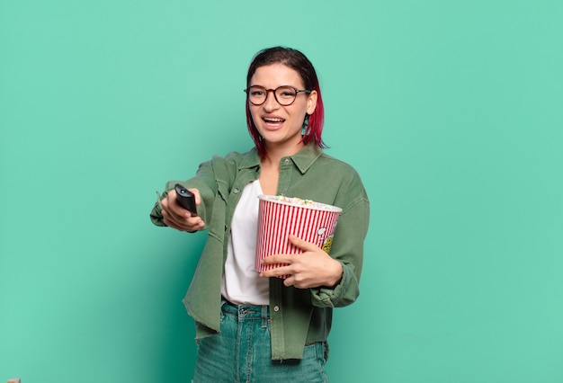 Femme cool cheveux roux avec des pop-corn et une télécommande de télévision