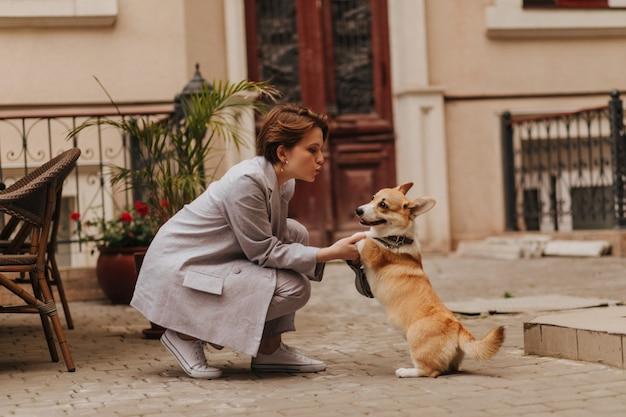 Femme cool en tenue grise joue avec le corgi à l'extérieur. jolie fille en veste et pantalon surdimensionnés étreignant son chien