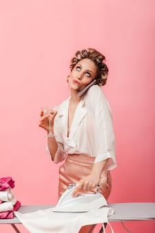 Femme coquette lève les yeux pensivement, parle au téléphone, boit du martini et repasse le linge