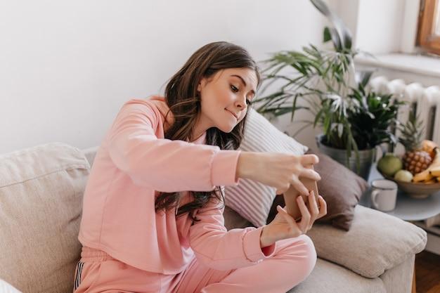 Femme coquine en survêtement joue la course sur son téléphone, assis sur le canapé