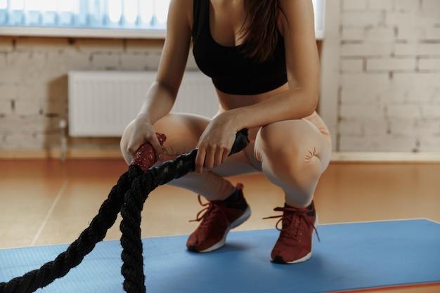 Femme avec des cordes de combat exercice dans la salle de fitness. athlète, sport, corde, entraînement, entraînement, exercices et concept de mode de vie sain