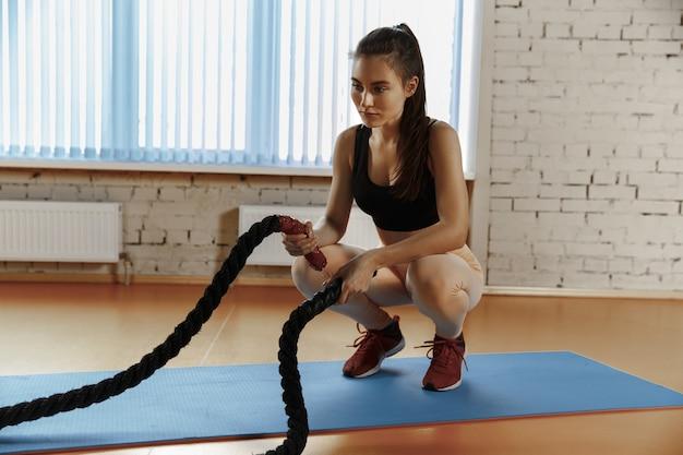 Femme avec des cordes de combat exercice dans la salle de fitness.