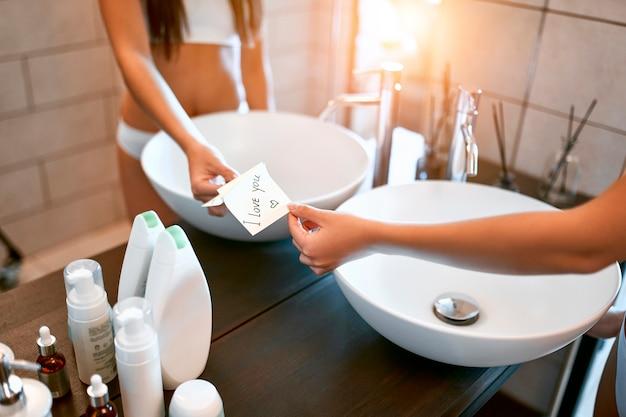 Une femme coréenne en sous-vêtements blancs se tient dans la salle de bain devant un miroir et prend un autocollant avec l'inscription je t'aime de son petit ami. soins du visage et du corps.