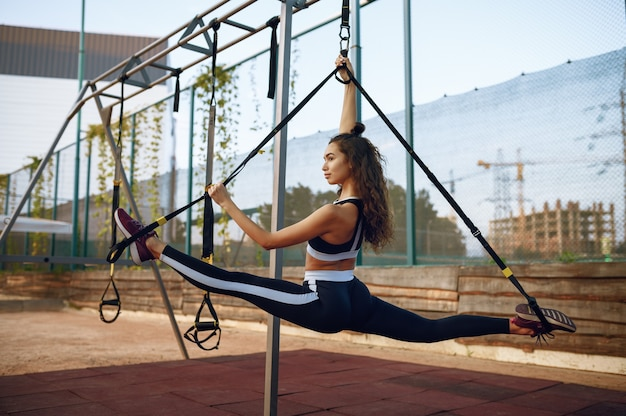 Femme avec un corps parfait faisant des exercices d'étirement avec des cordes sur un terrain de sport à l'extérieur