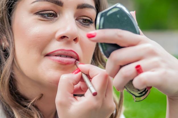 La femme corrige le maquillage et la coiffure dans le parc. femme mettant, corrigeant le brillant à lèvres au rouge à lèvres rouge.