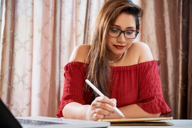 Femme corrigeant le document sur l'ordinateur tablette