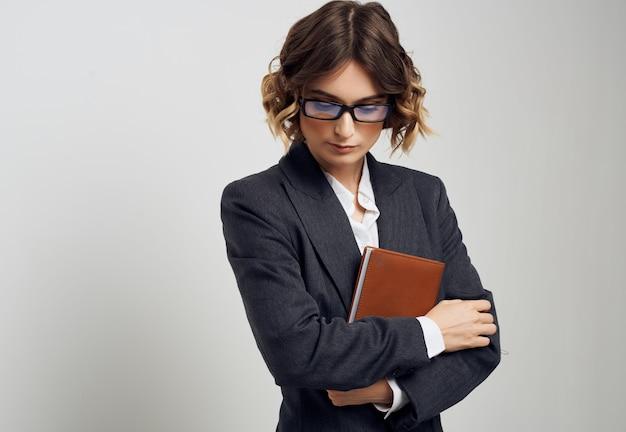 Femme en costume d'affaires documents à la main fond clair