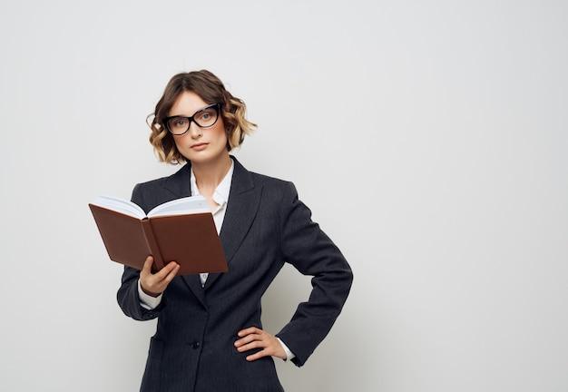 Femme en costume d'affaires avec un livre dans ses mains fond isolé