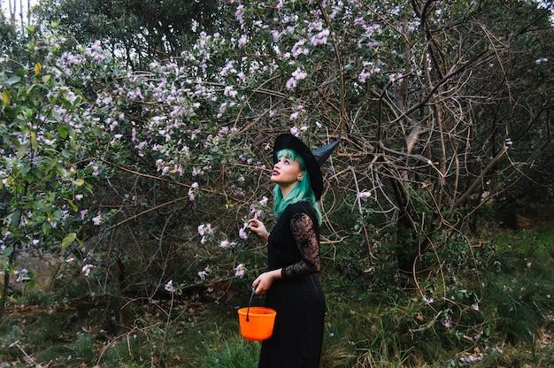 Femme en costume à l'arbre en fleurs