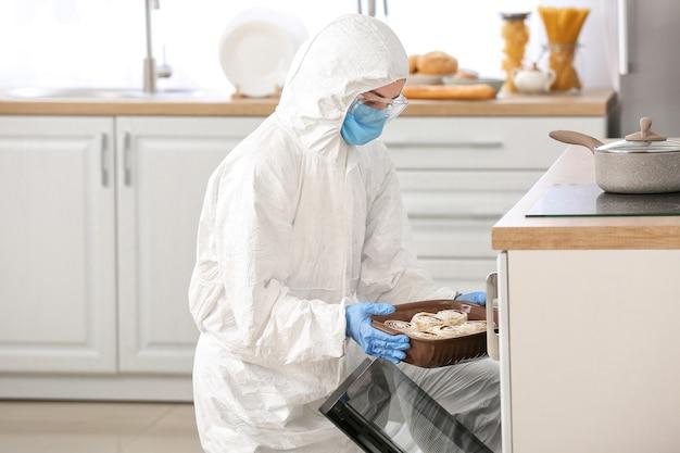 Femme en costume biohazard cuisine dans la cuisine