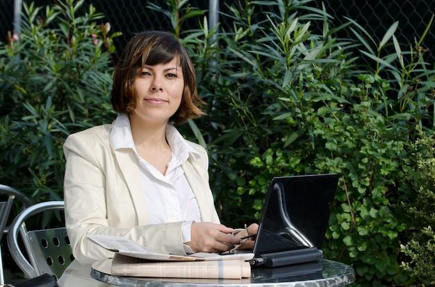 Femme en costume blanc assis à une table avec son ordinateur portable près des buissons verts