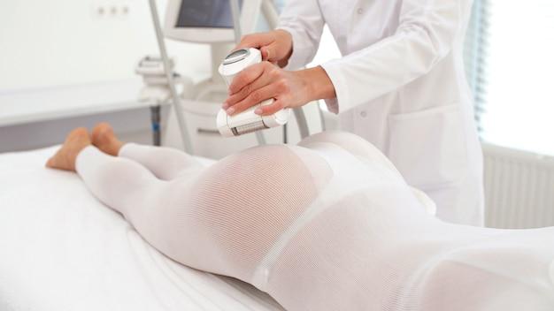 Une femme en costume blanc spécial reçoit un massage lpg anti-cellulite