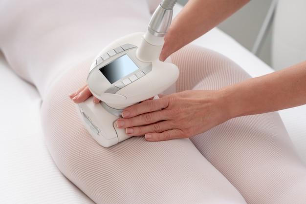 Femme en costume blanc spécial se massage anti-cellulite dans le salon spa. soin lpg et contour du corps
