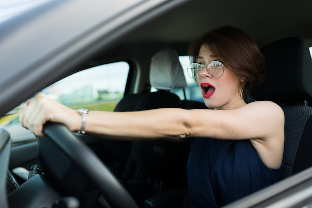 Femme en costume de bureau ariives au travail en voiture et besoin d'aide