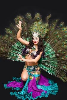 Femme en costume de carnaval de plumes de paon assis sur le sol, isoler fond noir