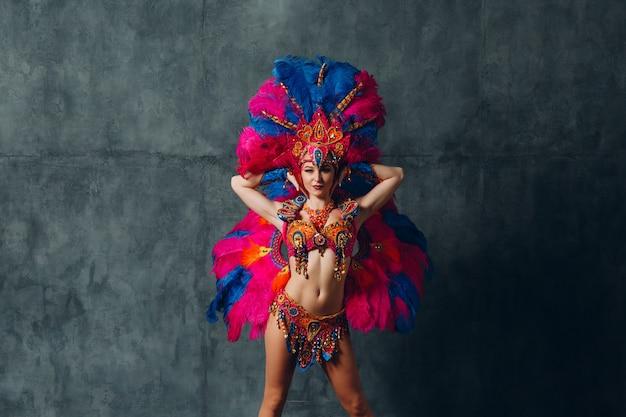 Femme en costume de carnaval samba brésilien avec plumage de plumes colorées.