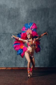 Femme en costume de carnaval de samba brésilienne avec plumage de plumes colorées.
