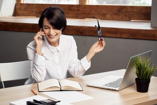 Femme en costume devant le secrétaire d'ordinateur portable fond clair exécutif