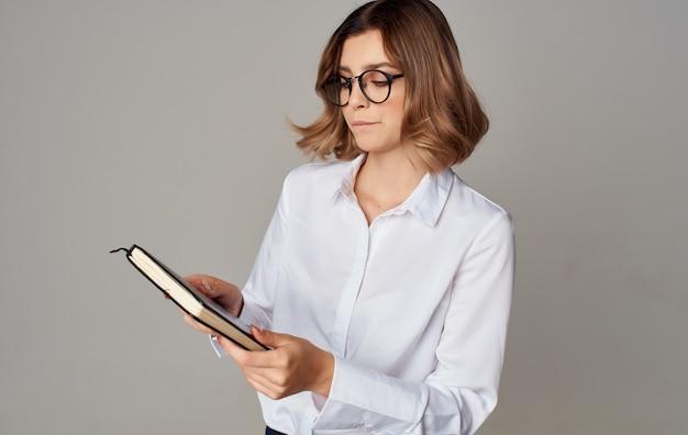Femme en costume avec des documents à la main fond clair de travail