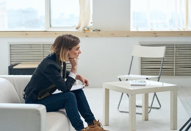 Une femme en costume est assise sur le canapé avec des documents près de la fenêtre. photo de haute qualité