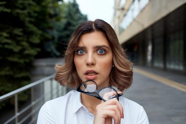 Femme en costume à l'extérieur avec des documents en main fond clair