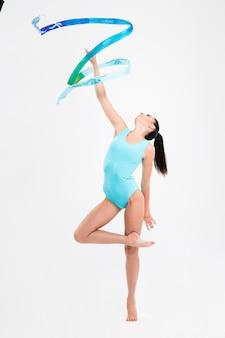 Femme en costume de gymnaste montrer des compétences athlétiques isolé sur un mur blanc
