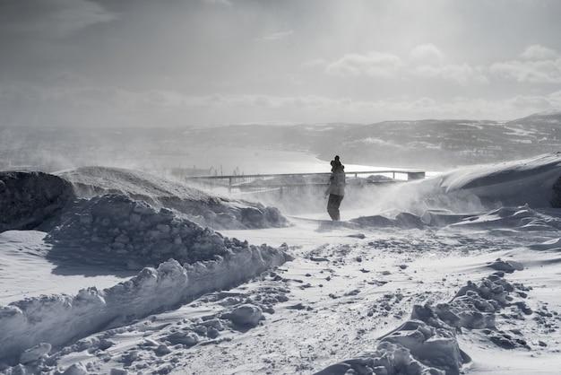 Femme en costume d'hiver dans le contexte d'un champ couvert de neige