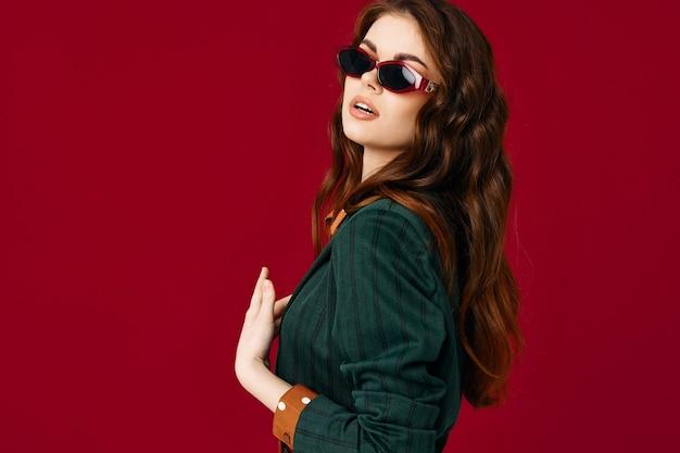 Femme en costume lunettes de soleil posant fond rouge glamour